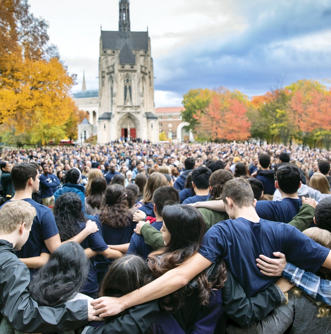 Pitt community members stand on Cathedral lawn and put arms around each other's shoulders.