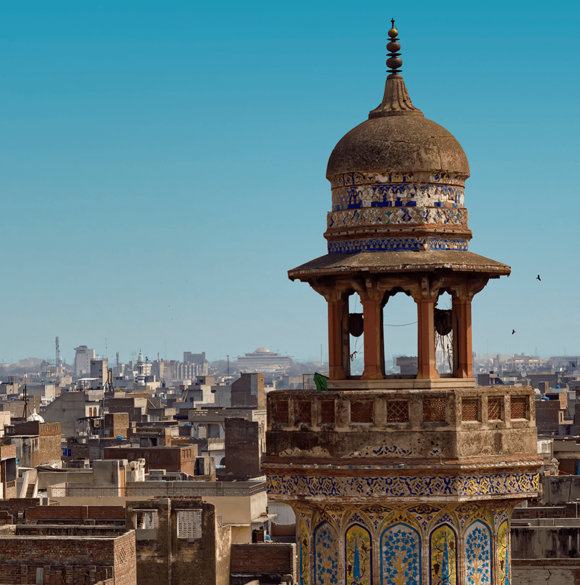 Spire of mosque against the blue sky, with tan-and-brown cityscape in background