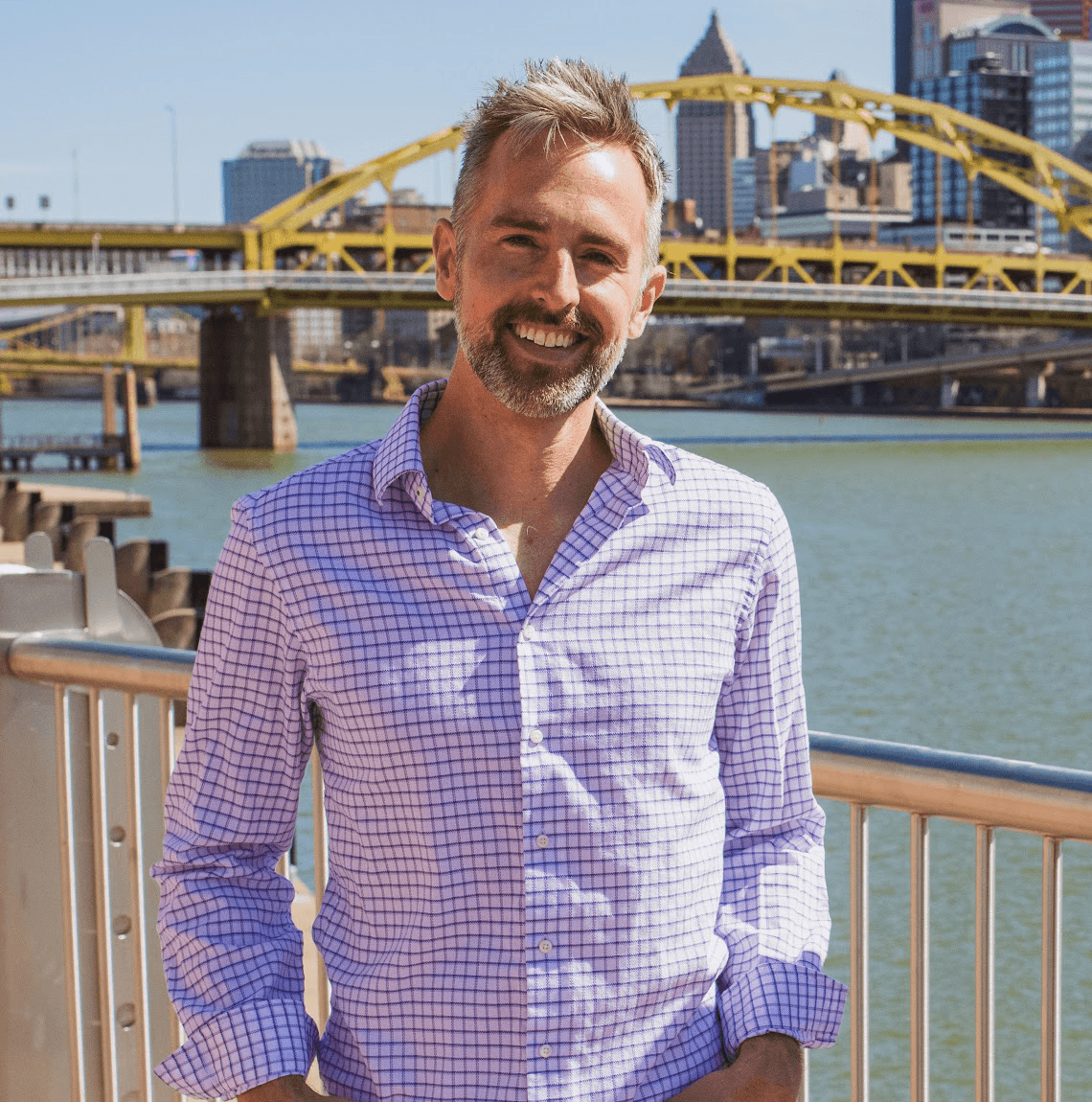 photo of White man with gray hair and beard in button-down shirt stands in front of river, bridge and cityscape