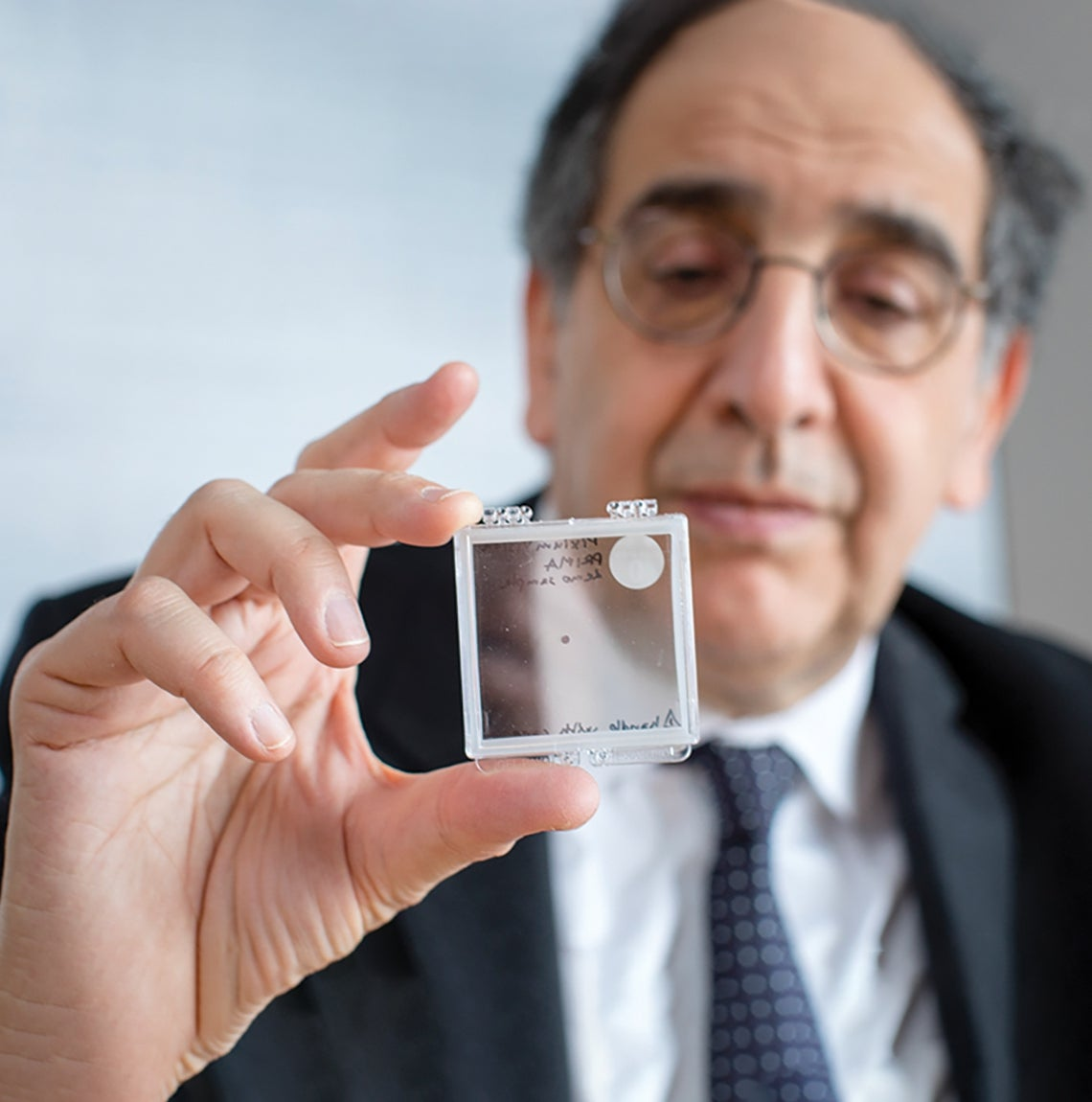 main in dark suit holds glass slide in focus for camera