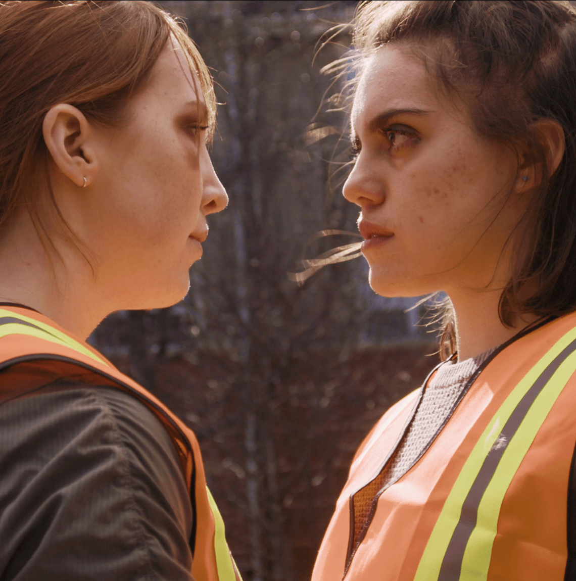 two young women wearing orange safety vests look each other in the eye while standing outside in the sun