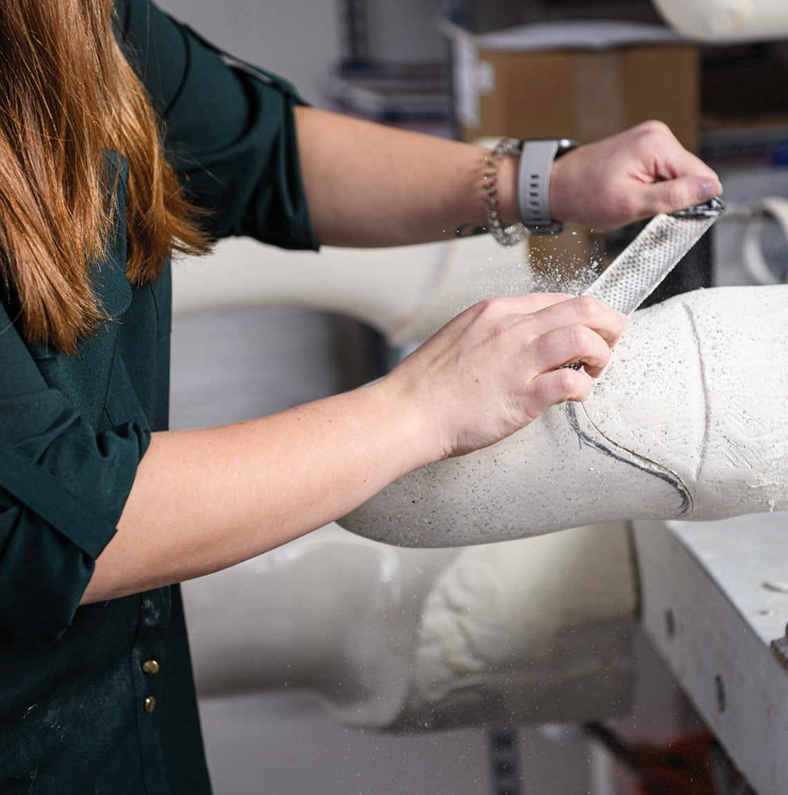 With the plaster cast of a patient's residual limb held in place on her work bench, Caulfield files the surface smooth.