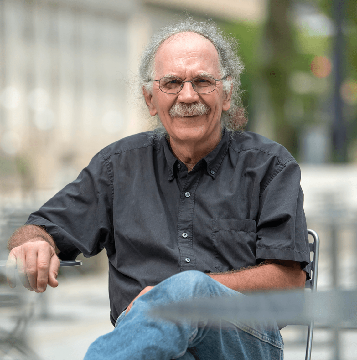 white man with gray curly hair, mustache wearing dark gray button-down and blue jeans